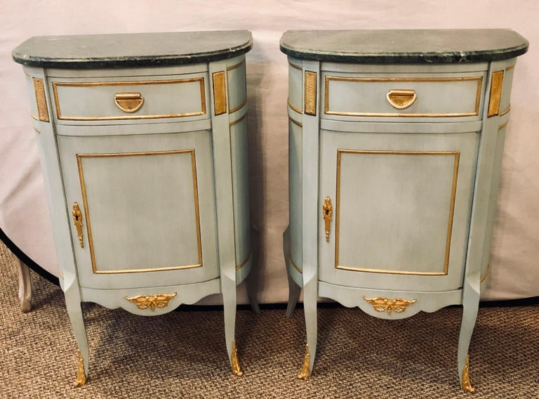 A finely constructed pair of green blue painted marble top Louis XV style nightstands, side tables or/ end tables. Each in the Louis XV style with bronze mounts and marble tops. The demilune painted cabinets with a single shelved door under one