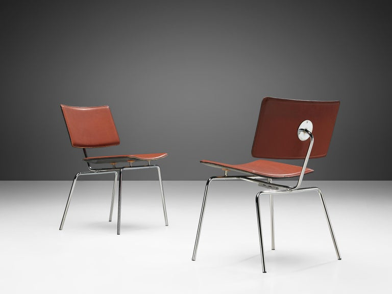 Pair of dining chairs, leather and chrome, Europe, 1970s.  Curved leather seat and back supported by elegant chrome frame. Simple but not boring. The red leather and the large chrome single fastening at the back of the chair makes it an existing