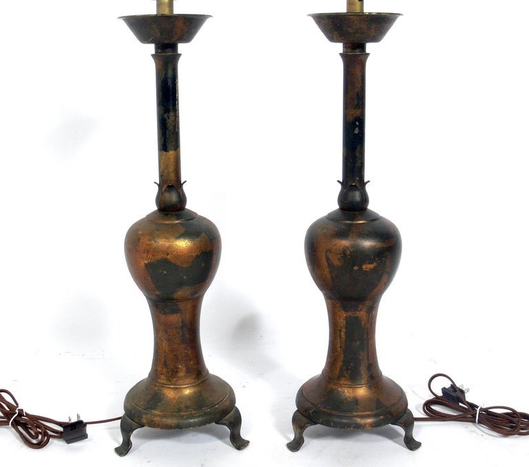 Pair of distressed gilt metal Asian lamps, probably Chinese, circa 1950s, possibly earlier. They have been rewired and are ready to use. The price noted below includes the shades.