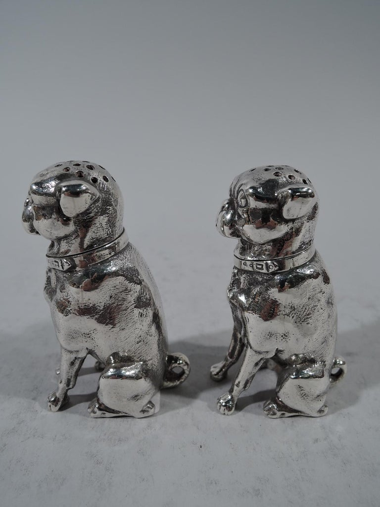 Pair of sterling silver dog-form salt and pepper shakers. Made by Dominick & Haff in New York in 1879. Each: cast figure of stocky seated pup with stiff forelegs and curlicue tail. Flat face with exophthalmic eyes and short snout. Head pierced and