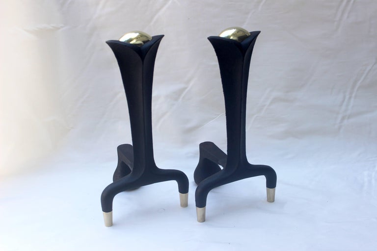 Pair of Donald Deskey andirons made of cast iron and brass.