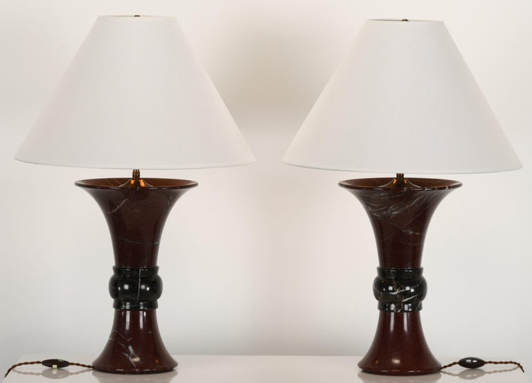 A pair of Donghia marble two-tone Griotte red marble with white veining mixed with Belgian black and white marble center table lamps. Shades not included. Lamps are in very good condition labeled
