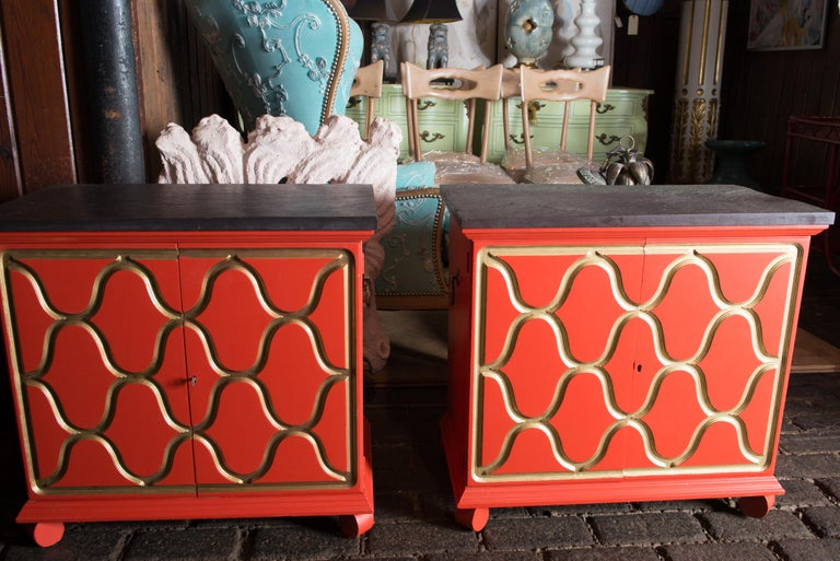 A pair of reddish-orange with gold trim Espana chests designed for Henredon by the premiere decorator, Dorothy Draper in the mid 1950s. They are finished with the original natural slate tops.