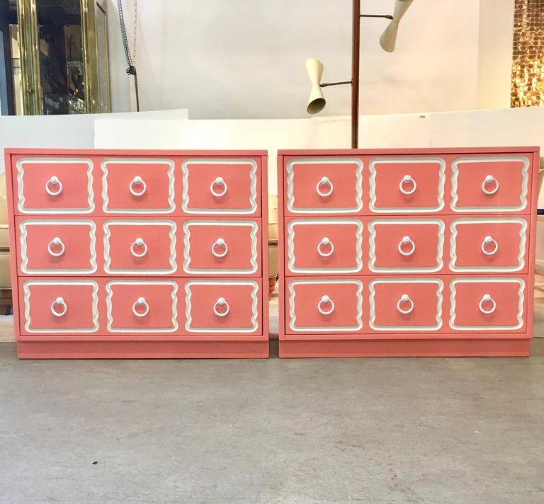 Pair of vintage Dorothy Draper España bunching chests of three drawers which we have newly refinished in Lyford Cay pink, white trim and white powder coated original ring pulls. These are total sunshine on a rainy day. Great color: soft pink with a