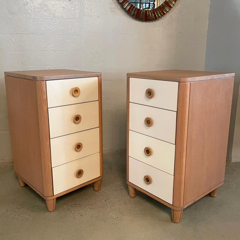 Pair of slim, highboy, 4 drawer pickled oak dressers by Raymond Loewy for Mengel feature a two-tone finish in blush pink with cream drawers. The drawers measure 14 W x 16 D x 6 H inches.