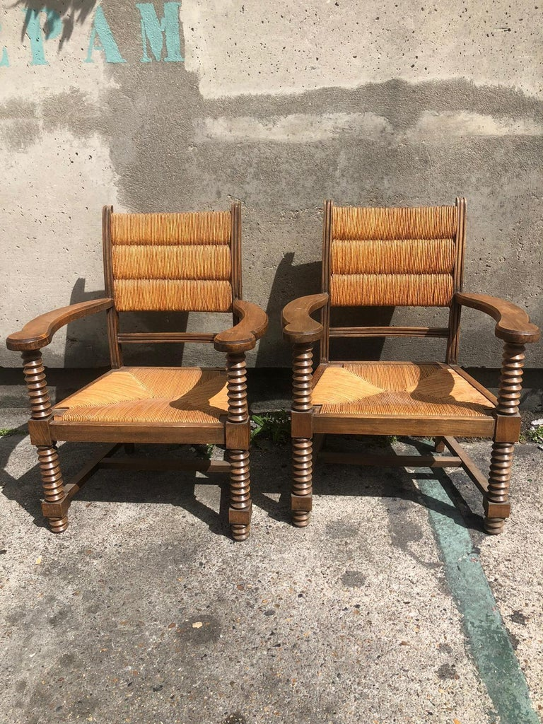 A pair of Dudouyt armchairs in oak and straw.
