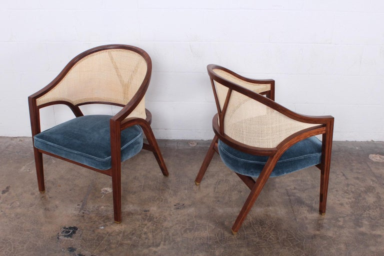 A pair of cane back lounge chairs with brass feet and mohair upholstery.