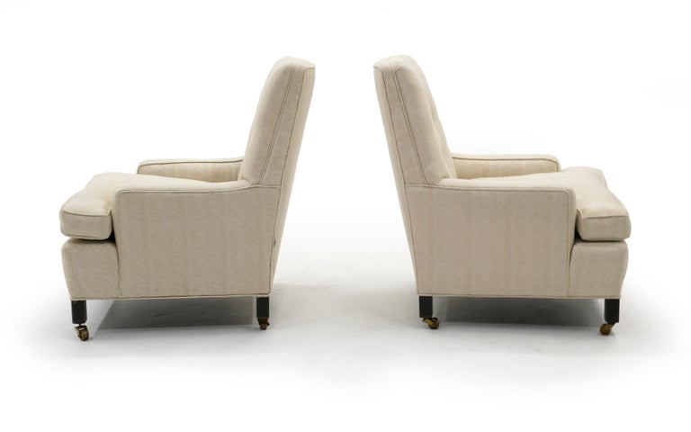 High back medium scale pair of lounge armchairs designed by Edward Wormley for Dunbar. Slightly tapered tufted inside backs and down filled seat cushions. Original mahogany legs with solid brass casters. There are various spots on the fabric so