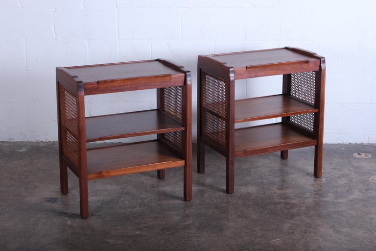 A pair of walnut nightstands with cane sides. Designed by Edward Wormley for Dunbar.