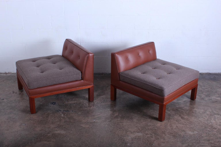 A versatile pair of slipper chairs with mahogany frames and leather/wool upholstery. Designed by Edward Wormley for Dunbar.