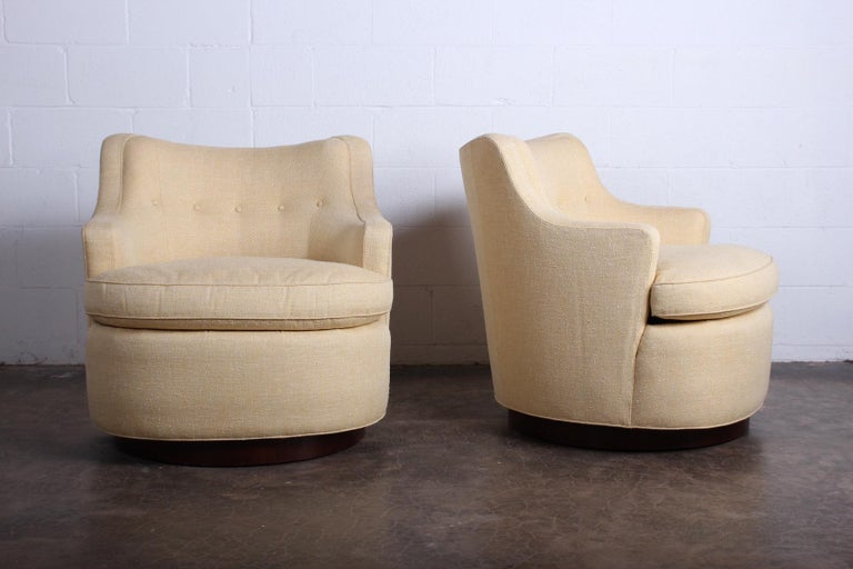 A pair of large scale swivel chairs on mahogany bases designed by Edward Wormley for Dunbar. Fully restored with down cushions and upholstered in Cowtan and Tout cotton in a neutral straw yellow weave.