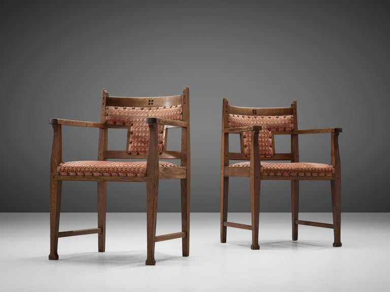 Pair of armchairs, oak, fabric, wood, the Netherlands, 1920s  Excellent pair of armchairs in oak, upholstered in red fabric that is attached with brass nails. The chairs are an excellent example of the 'Amsterdamse School' style. These chairs have a