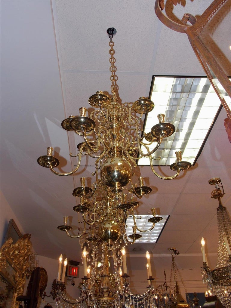Pair of Dutch colonial brass two-tiered twelve light chandeliers with scrolled decorative arms, original bobeches, centered bulbous column, and terminating on a large ball with centered ring finial. Chandeliers are candle powered and can be