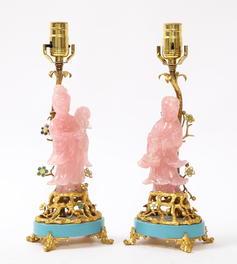 A fantastic pair of marked E. F. Caldwell and Co. Louis XVIstyle dore bronze mounted hand-carved rose quartz and enamel table lamps. Mounted on two dore bronze open work bases with blue enamel decoration and dore bronze Asian inspired feet are two
