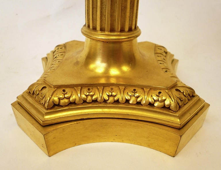 This beautiful pair of gilt bronze lamps feature neoclassical motifs, including urn form finials, bow knots, and acanthus leaves.