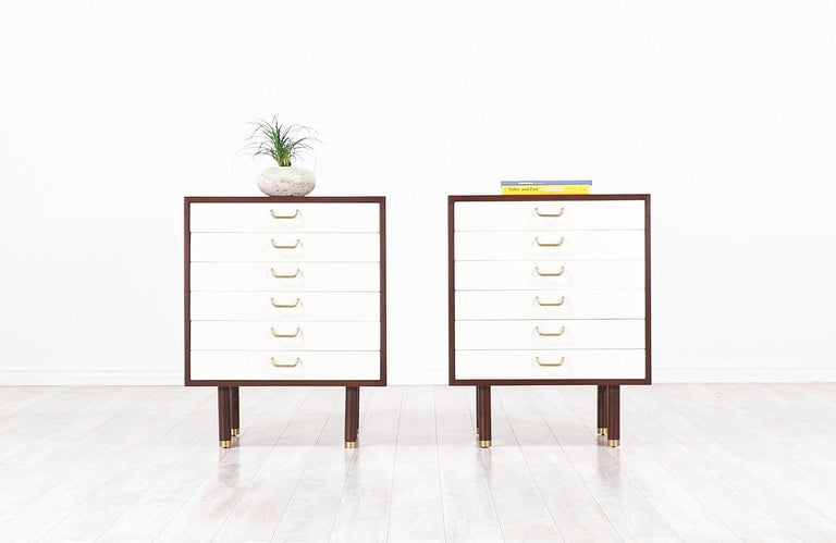 A pair of beautiful nightstands or chests designed by E. Gomme and manufactured for G-Plan in the United Kingdom, circa 1960s. Comprised of walnut-stained mahogany wood, each features six drawers which include the original brass handles and sabots