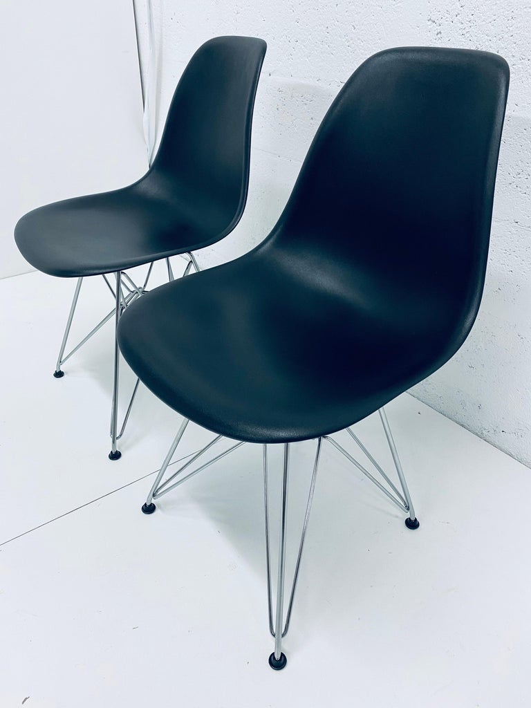 Two black moulded plastic side chairs with chrome Eiffel Tower bases by Charles and Ray Eames for Herman Miller, 2010s.  Charles and Ray Eames realized their dream to create a single-shell form over 80 years ago by making their molded chairs of