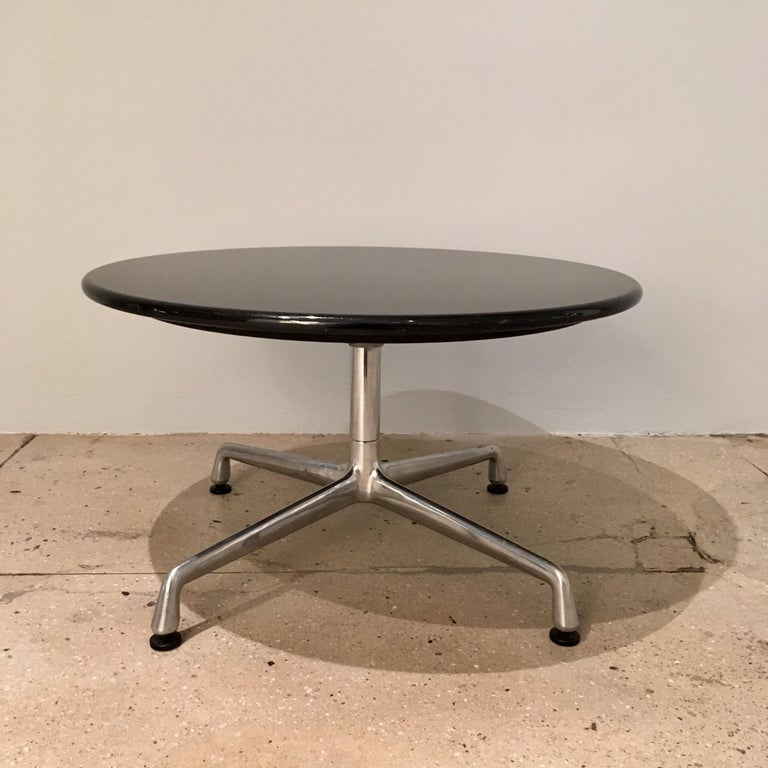 A pair of side tables composed of granite circular tops and sweeping aluminum legs design by Charles Eames for Herman Miller. Aluminum Group, 1960s.