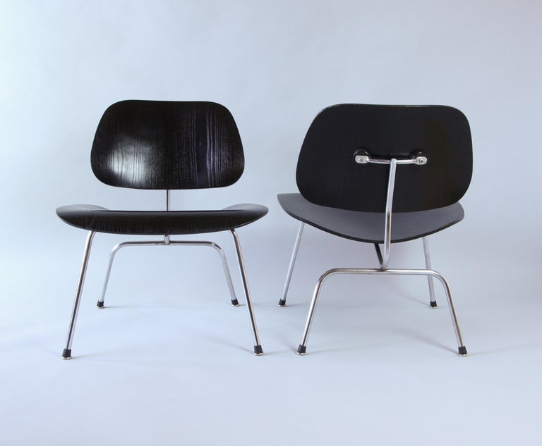 Two Eames LCM chairs in black and chrome, circa 1958. Great vintage condition showing age to the chrome with wear and scratching to the wood. Featuring the earlier style of angled rubber boot glides, these have been newly added. In 1957 Wily
