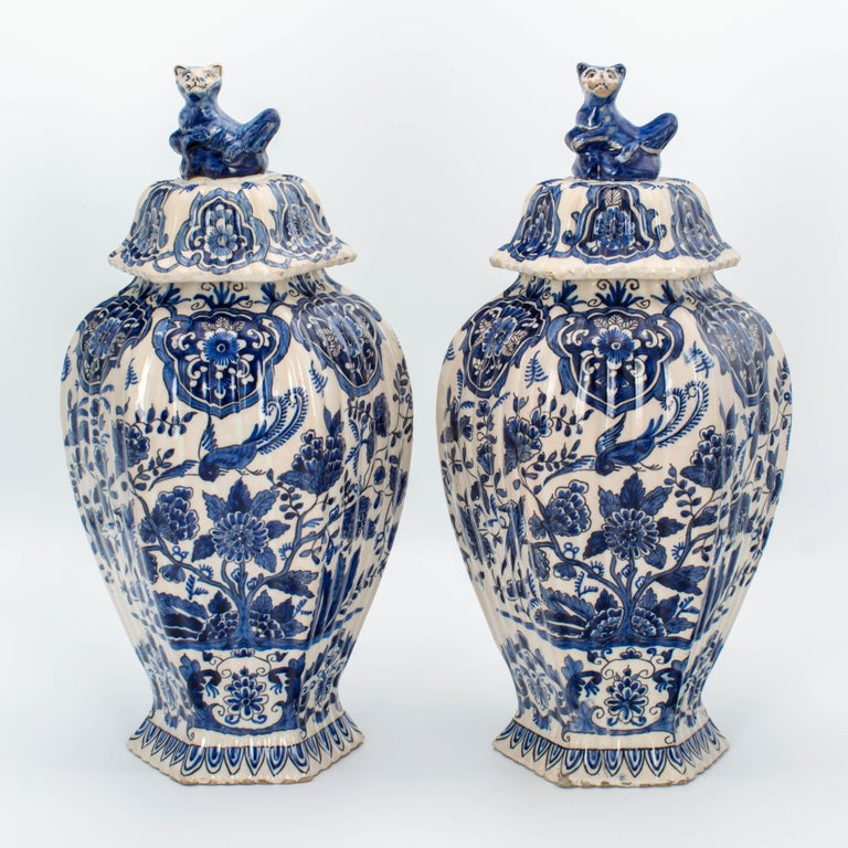 A pair of early 18th century delft faience lidded ginger jars with chinoiserie decoration of birds and flowers inspired by the blue on white decor of Ming porcelain. One bears the mark of Lambertus van Eenhoorn, who directed the ceramics factory De