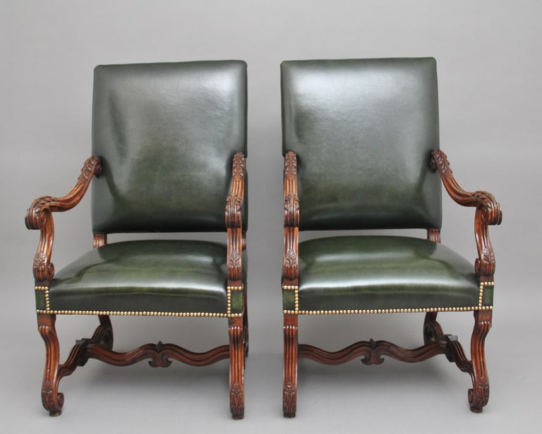 A superb pair of early 19th century French carved walnut armchairs, upholstered in green leather with brass stud decoration, shaped and carved arms with acanthus leaf decoration, supported on elegant shaped legs with carved scroll feet united by a