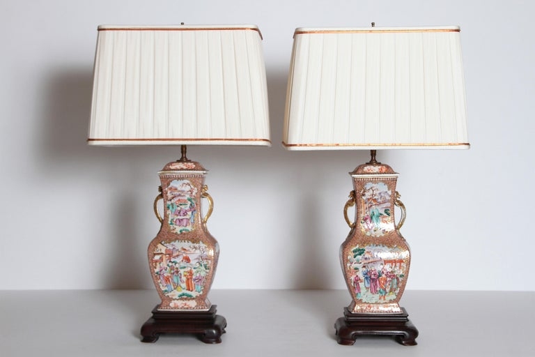 A pair of Chinese Export Rose Mandarin porcelain jars with lids as lamps. All four side have painted panels with people in landscapes on orange and gilt patterned background. A pair of gold lizards at the neck. Jars have been set on rectangular