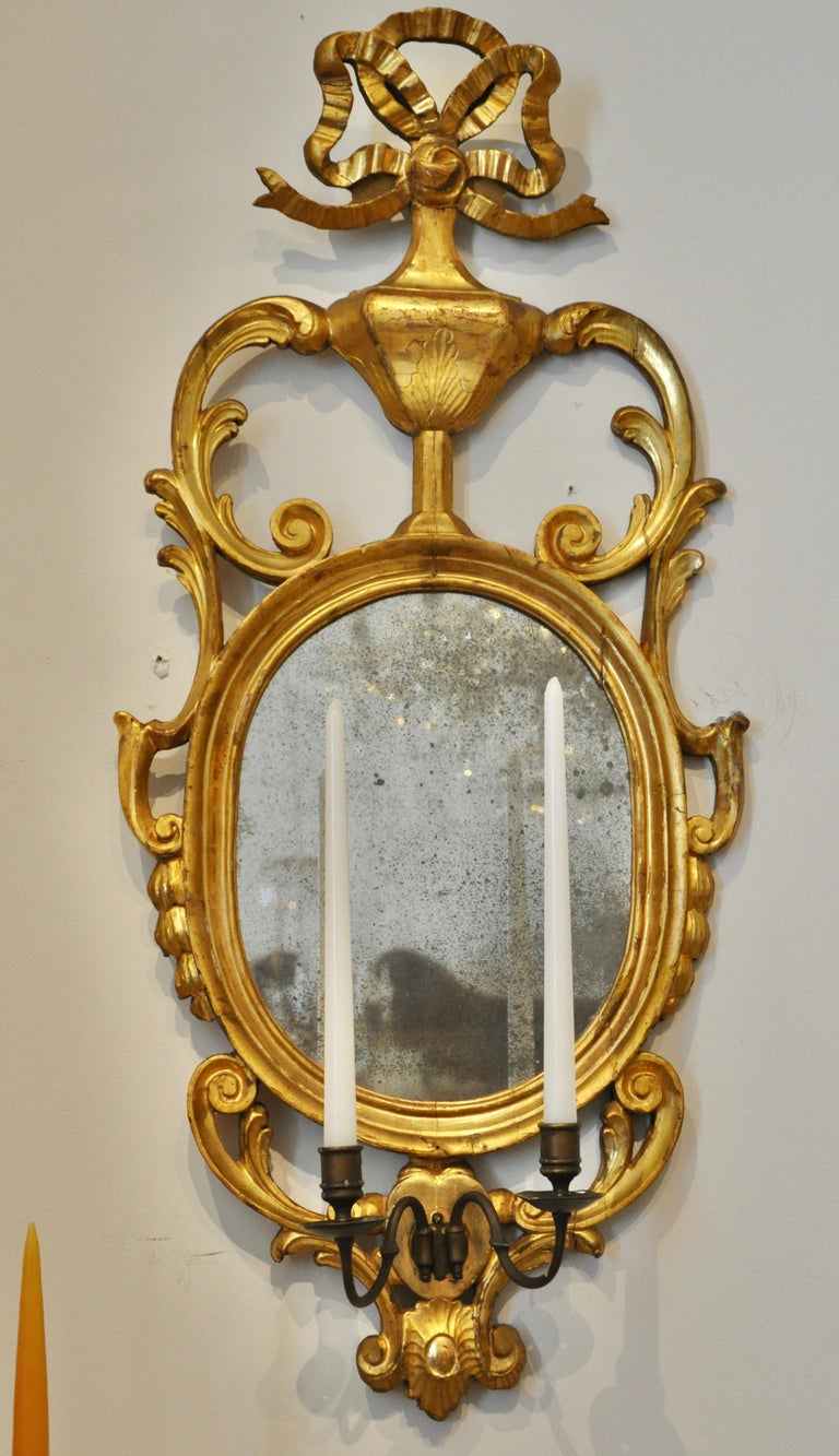 Pair of early 19th century continental sconce mirrors with original early glass and original gilding. Two arm sconces for candles. Great size and wonderful original water gilt carvings. Neoclassical ribbon top motif. Probably Danish in origin.