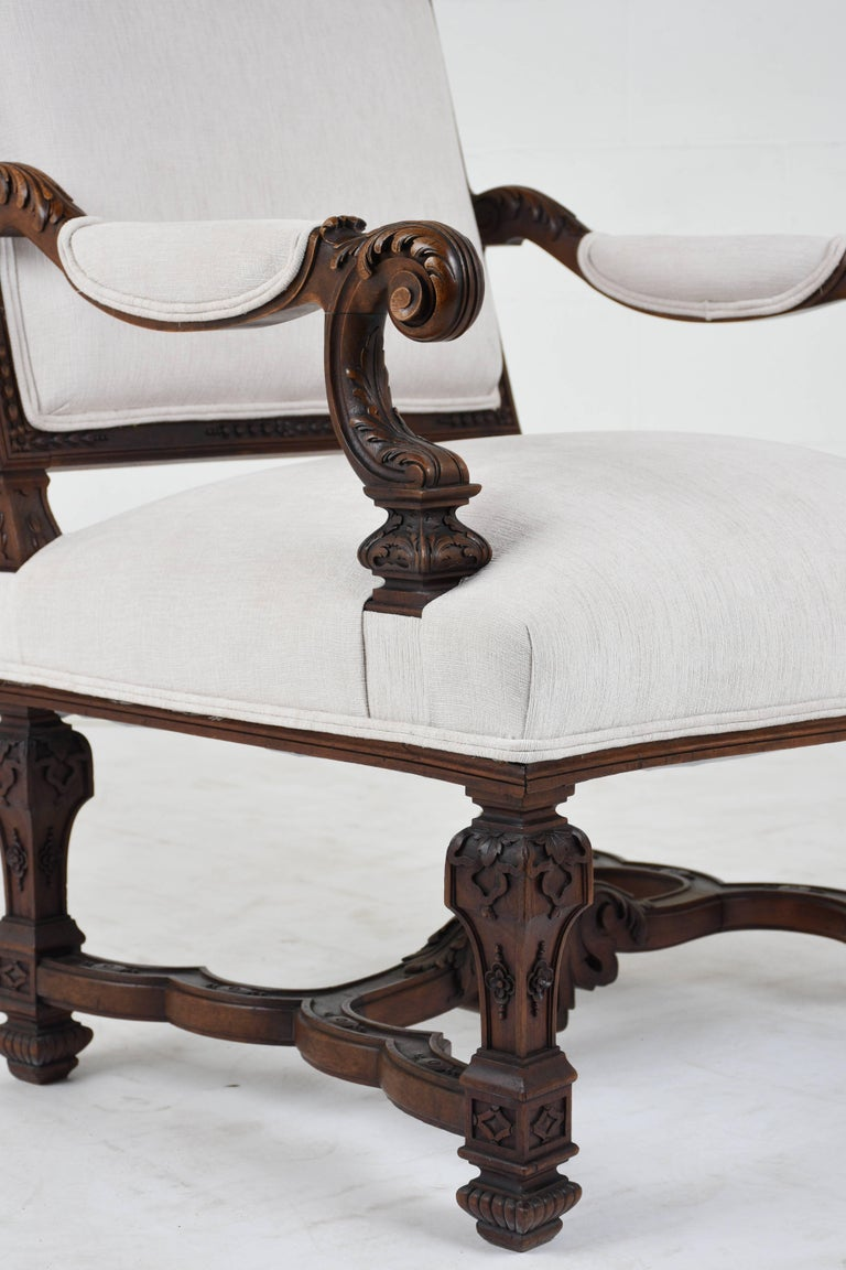 This pair of circa 1810s Louis XVI-style armchairs feature carved walnut wood frames stained a rich walnut color with a polished finish. The frames are adorned with classical motifs of acanthus leaves, scrolls, beads, and more. The comfortable seats