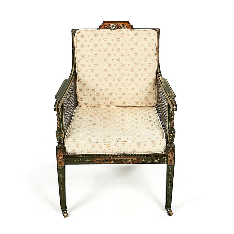 Pair of early 19th century Irish George III green and polychrome bergere armchairs. Each with a painted floral tablet crestrail and scrolled rectangular armrests. Loose cushions rest on the caned seat and back. The square-section tapering legs