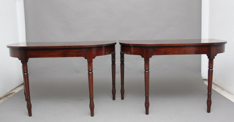 A pair of early 19th century mahogany console tables, the wonderfully figured demilune shaped top above a shaped apron, supported on elegant turned legs. The tables have a lovely nice warm rich mahogany color and both are in excellent condition,