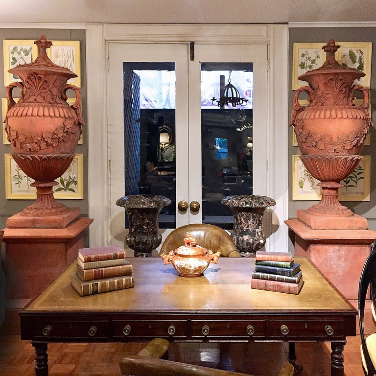 Each of this pair of large early 19th century terracotta campagna urns, in the neoclassical style, sits atop a molded socle plinth base, its baluster body ornamented with gadrooning, foliate and grape-vine motifs cast in relief, and with scroll