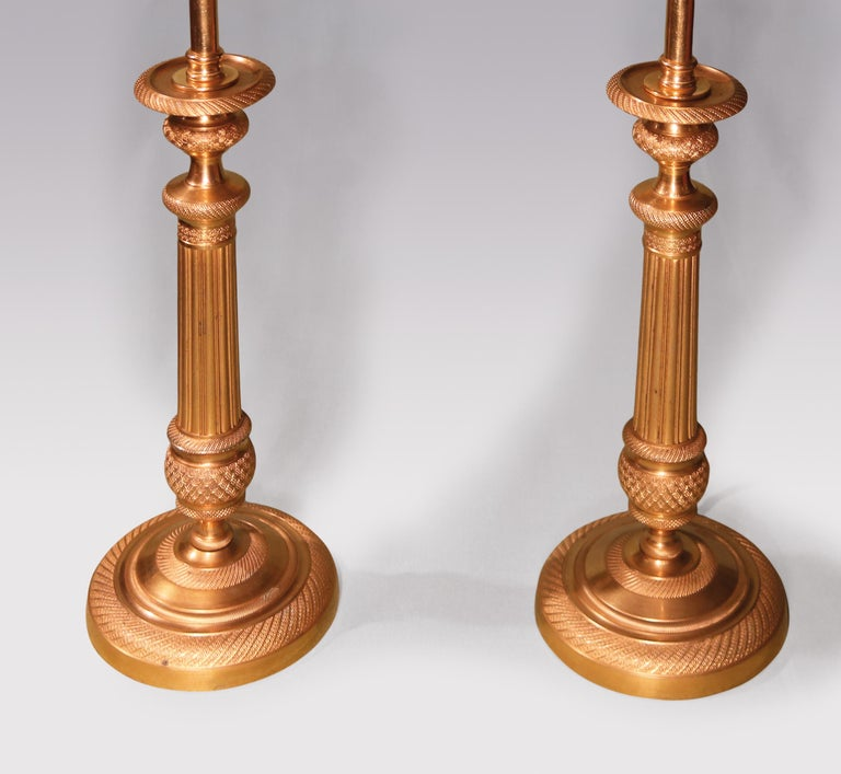 A pair of early 19th century ormolu candlesticks engine-turned throughout having urn shaped nozzles above reeded stems with circular bases. (Now converted to lamps) Height with shades: 20.75'.
