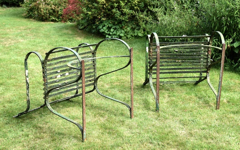 A fine and rare pair of English Regency period wrought iron garden armchairs, each with three strap back rails over a seat supported by 's' curved side frames and a bow-arched stretcher. Showing a multitude of ancient coats of paint and many years