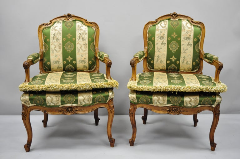 Pair of early 20th century French Louis XV style green and gold walnut fauteuils armchairs. Item features green and gold silk fabric, loose pillow cushions, solid wood frame, upholstered armrests, finely carved details, cabriole legs, quality