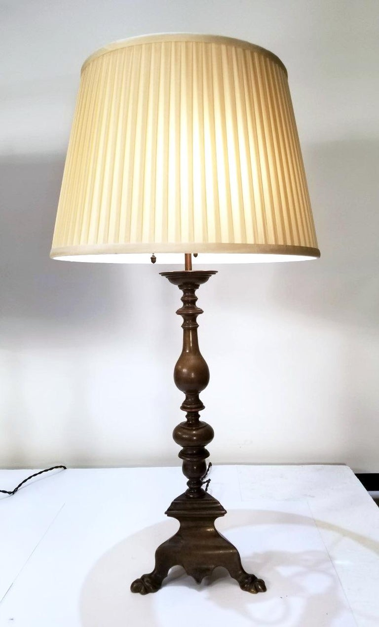 These elegant pair of Caldwell lamps are in the Baroque style and bear a Tripod base with Baluster stem that is finished in a beautiful hand rubbed Bronze finish. These lamps come with the original three light cluster and acorn pull chains.  Extra