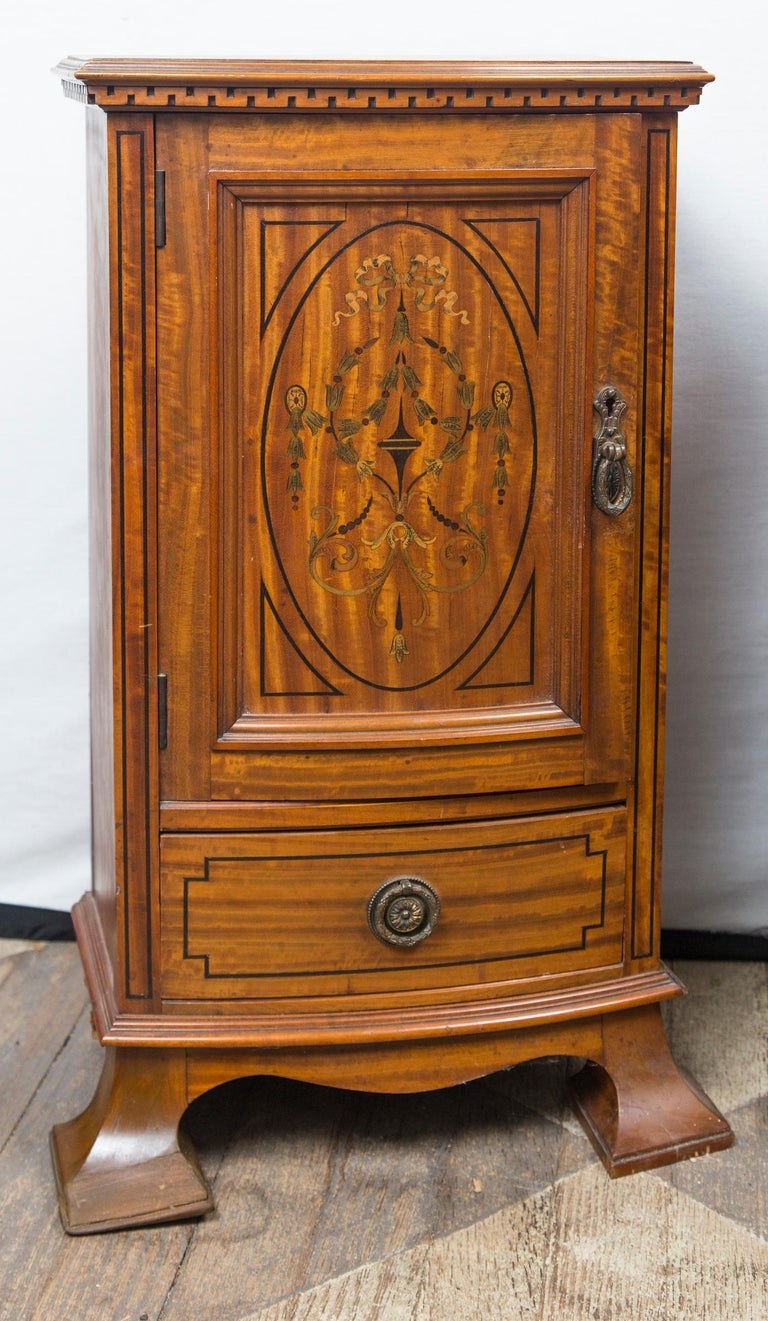 Each door front, inlaid with colored bell flowers and ribbons. With is a shelf.