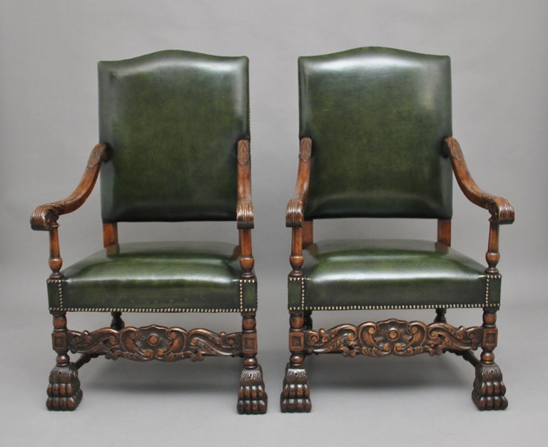A decorative pair of early 20th century carved armchairs in the Carolean style, upholstered in green leather with brass stud decoration, shaped and carved arms with acanthus leaf decoration with finely turned arm supports, standing on bold carved