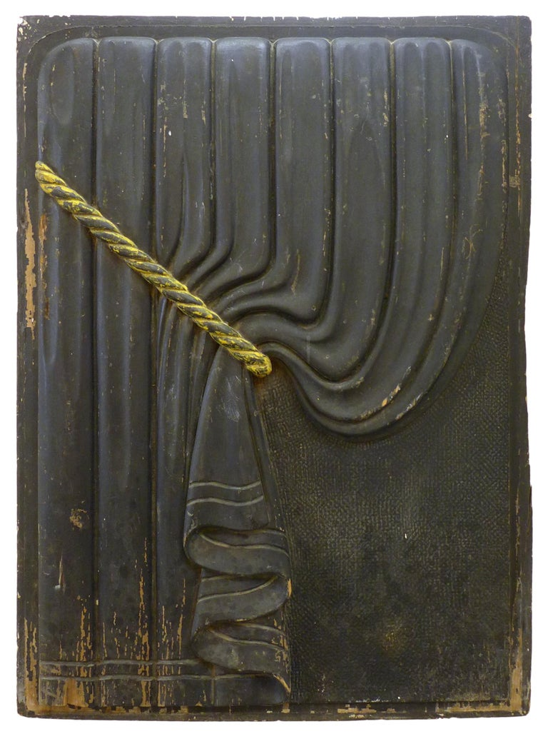 A wonderful pair of early 20th century, carved wood, funeral-coach curtain panels. A mirror-matched pair of matte black, bas-relief curtains with contrasting, gilt rope tiebacks. These sorts of panels were traditionally used as symbolic trompe