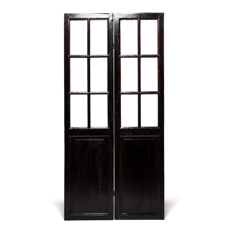 A hallmark of Qing-dynasty domestic architecture, these hand carved doors were originally used in a Provincial courtyard home to allow light and air into a room while maintaining privacy. Paned glass balances the dark-lacquered elmwood frame,