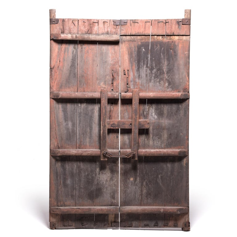 This imposing set of doors is over a century old and likely once opened onto the courtyard of a Qing-dynasty home in China's Shanxi province. Made of elmwood, the doors have developed a worn, rustic appearance over the decades exposing the wood