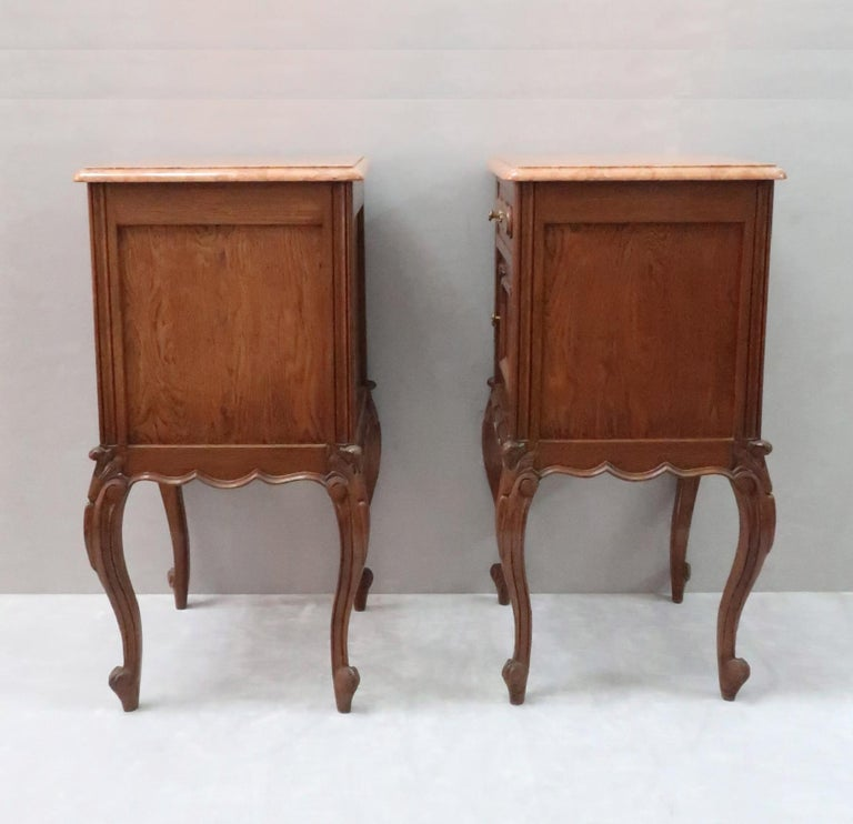 A good quality pair of continental oak bedside cabinets with carved and molded decoration. The cabinets have a storage cupboard and drawer to the front with brass knobs and a tan colored mottled marble top.