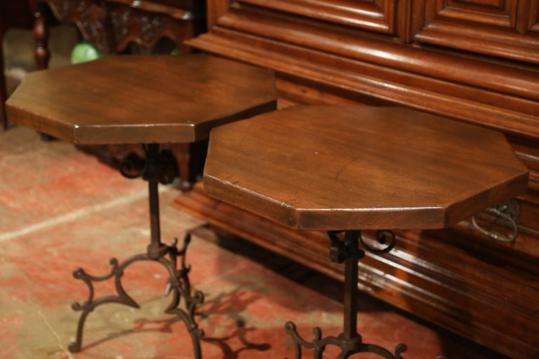 Place this pair of Gothic style side tables on either side of a sofa as end tables; probably crafted in Spain circa 1920, each table features a fruitwood octagonal top sited on a three-leg wrought iron base with scroll decor. Both tables are in