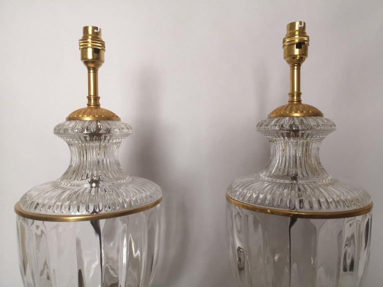 Pair of high quality early 20th century French crystal lamps. With ribbed bodies, gilt rim and base. French, circa 1920.