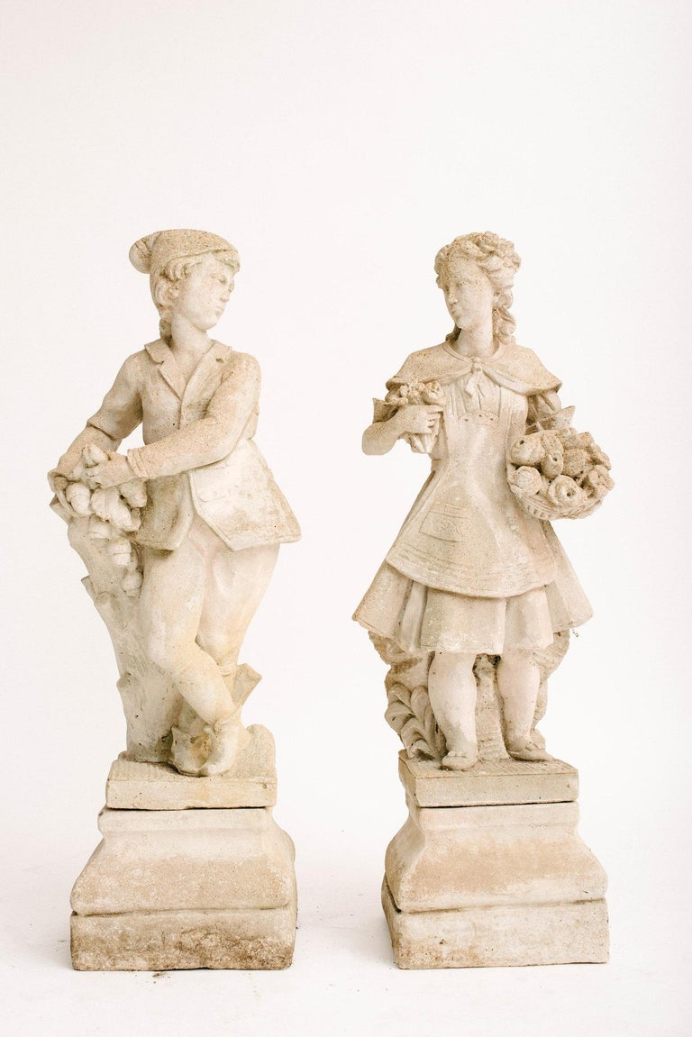 A lovely pair of 20th century concrete garden figures from France. He is perched next to an oak stump with foliage and acorns in hand. She carries two floral bouquets. These figures both sit atop two separate pedestal bases.