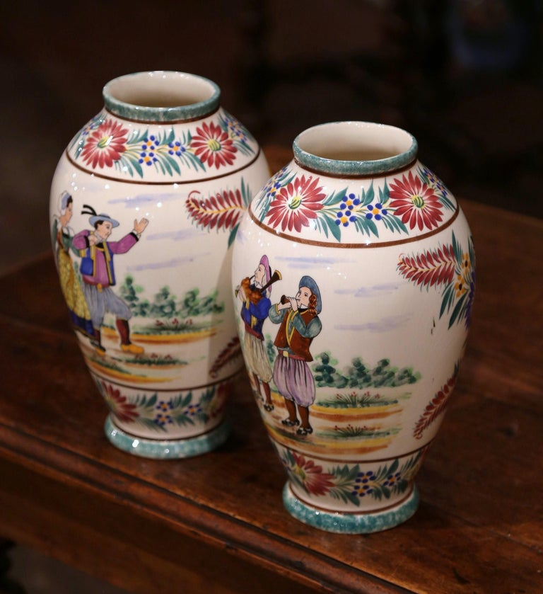 Decorate a mantel or table with this colorful pair of antique faience vases. Crafted in Brittany, France, circa 1930, both hand-painted vases are round in shape, and depict Britons people dressed in traditional outfits. One vase features a couple