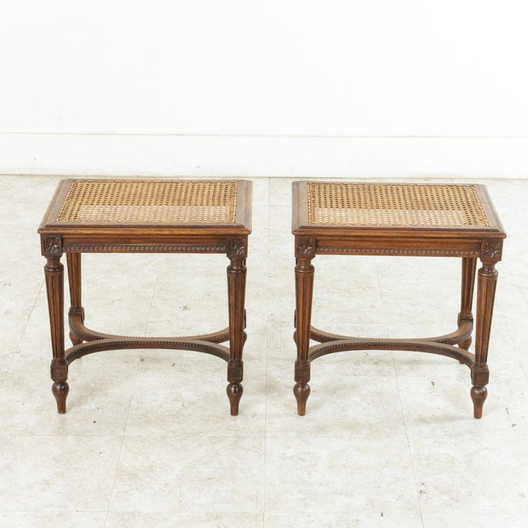 This pair of early 20th century French Louis XVI style benches or banquettes features caned seats in pristine condition. Carved detailing of Classic rosettes adorn the die joints, and a carved rais-de-coeur pattern surround the apron. The seats rest