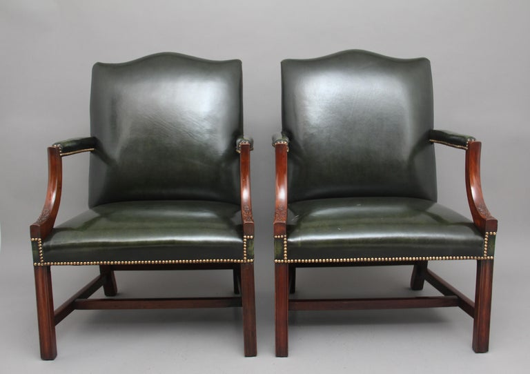 A pair of early 20th century mahogany Gainsborough / library open armchairs, upholstered in green leather with brass stud decoration, having padded arms and shaped arm supports carved with flowers, supported on moulded square legs united with