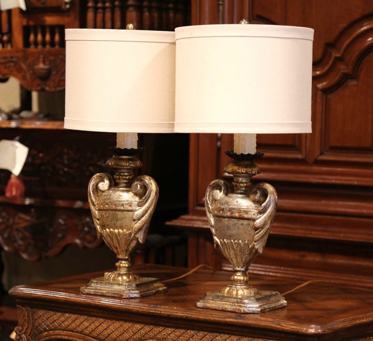 Place these elegant antique lamps on a pair of bedside tables or on top of a console in an entry! Crafted in Italy circa 1920, each hand carved lamp sits on a square base and features a Medicis vase shaped embellished with carved leaf handle motifs.