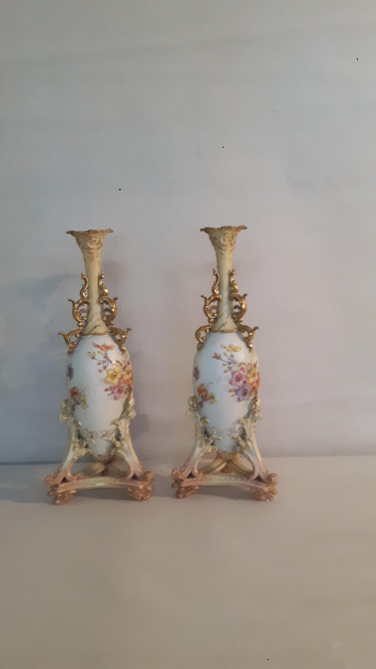 A pair of Rudolfstadt Porcelain vases, very much in the Royal Worcester style, hand painted with floral subjects on a duck-egg background; the neck and foot of the vases decorated with bisque and gilt scrolls the necks enhanced by a gilt Florentine