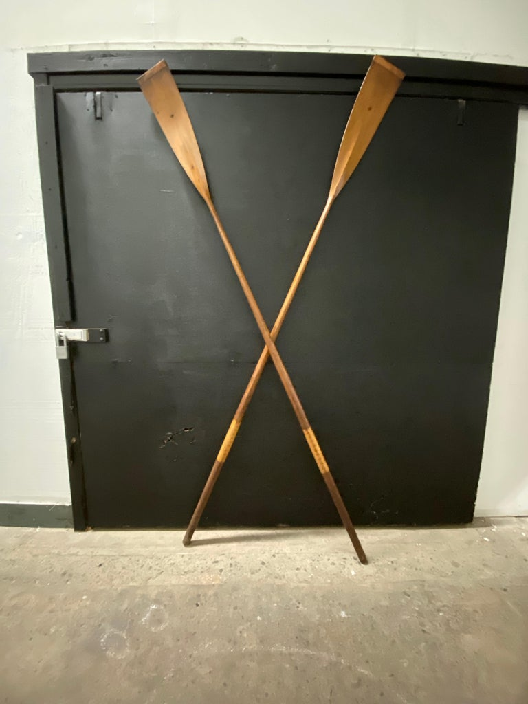 Pair of early handmade crew blades (oars) by The New York Boat Oar Company, 69 West Street. Made of an amazing light, weight yet durable wood. hand-sculpted for maximum pull whether you are sculler or a one person sweeper. Copper clad edges. The
